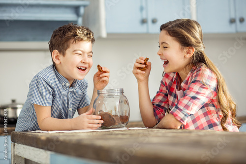 Joking. Cute happy little dark-haired brother and sister laughing and eating cookies while sitting at the table