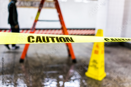 Obraz Caution tape sign in underground transit empty large platform in New York City NYC Subway Station in Grand Central, ladder, wet floor cone - fototapety do salonu
