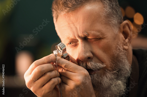 Foto  Jeweler evaluating gem with magnifier at workshop