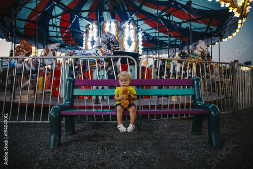 Poster Amusementspark Portrait of baby girl holding toy while sitting on bench at amusement park