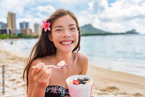 Acai breakfast smoothie bowl eating woman enjoying hawaii food on Waikiki beach, Honolulu. Asian girl happy smiling on detox diet eating healthy local fruit snack.