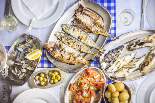 Barbecued sea bass, golden, horse mackerel accompanied with tomato salad, clams, bread and white wine