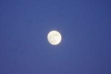 Full Moon Shining In The Bright Blue Sky