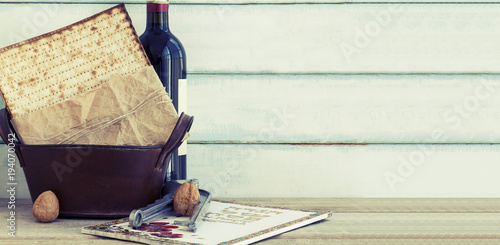 Pack of matzah or matza, Passover Haggadah and Kosher red wine on a vintage wood background. Jewish Passover holiday composition with copy space.Hebrew text translation: The story of Passover
