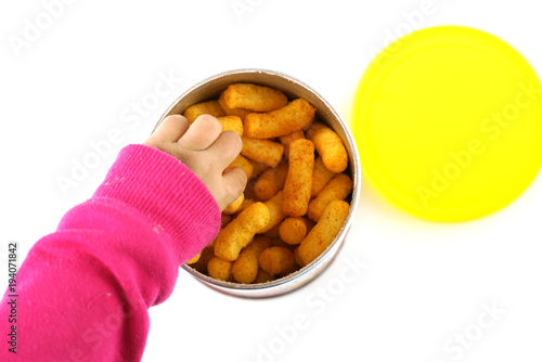 Fotografie, Obraz  Baby hand reaching for crunch baked snack in the container