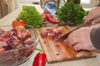 Cook hands with raw meat and vegetables in kitchen