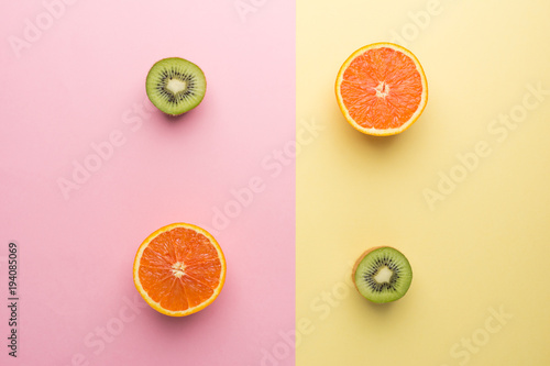 Creative Concept. Two Half Orange and Two Half Kiwi on Geometry Yellow Pink Pastel Background, Top View. - 194085069