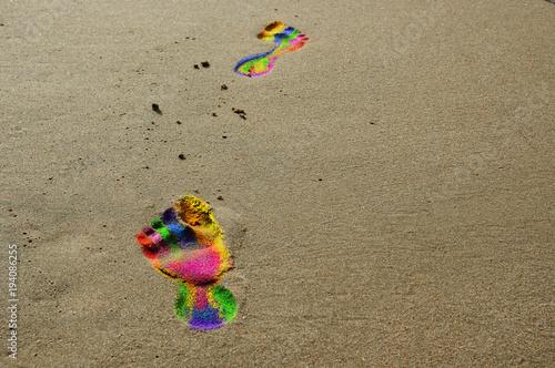 Fotografie, Obraz  Ślady stóp w kolorach tęczy na plaży.