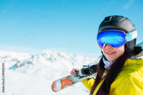 Fotografía  Portrait of sporty woman in helmet with skis on her shoulder against background