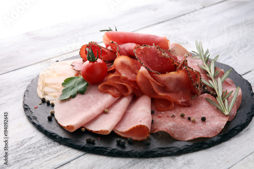 Fototapeta Food tray with delicious salami, pieces of sliced ham, sausage, tomatoes, salad and vegetable - Meat platter with selection obraz