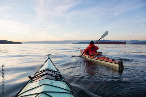 Man on Sea Kayak is kayaking during a vibrant winter sunset. Taken near Jericho Beach, Vancouver, BC, Canada.