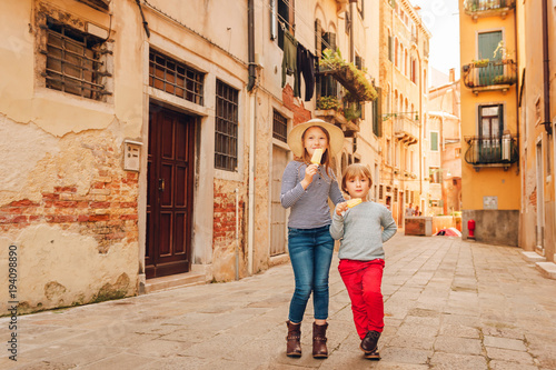 Poster Lieu connus d Asie Two funny kids walking through old italian streets, family tavel with children. Kids eating ice cream