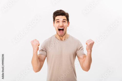 Photo of delighted brunette guy shouting and clenching fists like winner or luck Poster Mural XXL