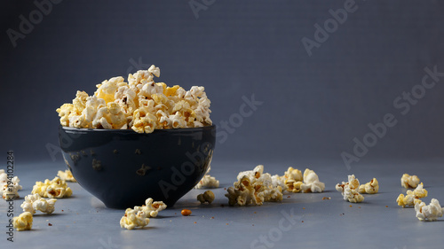 Popcorn in the bowl over grey background