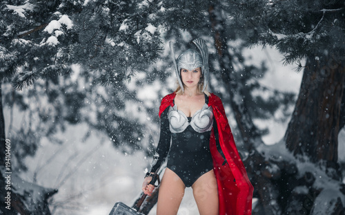 Fotografía  Woman in image of Germanic-Scandinavian God of thunder and storm stands with hammer in her hand