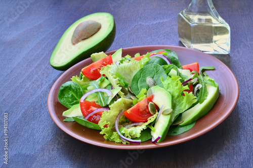 Fotografie, Obraz  Green tossed salad with  leafy vegetables, arugula, baby spinach, avocado, cherry tomatoes and pumpkin seeds