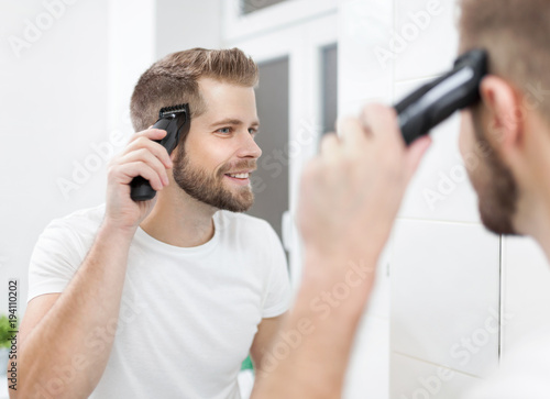 Fotografía Handsome man cutting his own hair with a clipper