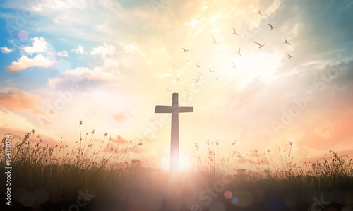 Fotografia  Ascension day concept: The cross on meadow autumn sunrise background