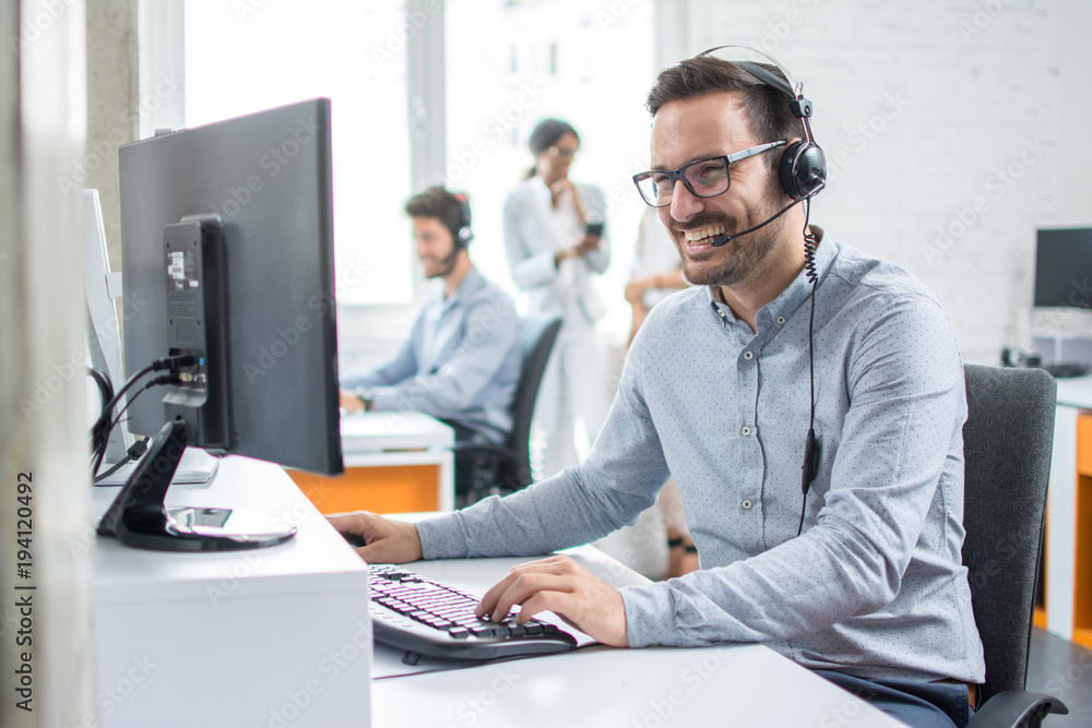 Fototapeta Smiling customer support operator with hands-free headset working in the office.