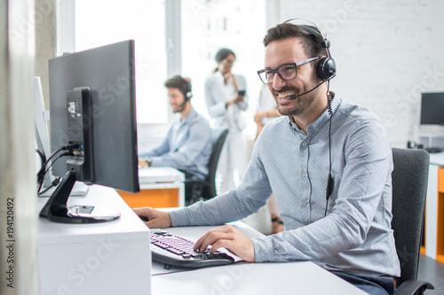 Smiling customer support operator with hands-free headset working in the office Fototapet