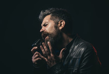 Life Style Concept - Handsome Man With Beard Wearing Black Leather Jacket Holding Microphone And Singing. Emotional Portrait Attractive Singer With Beard And Mustache. Bearded Man Singing Karaoke.