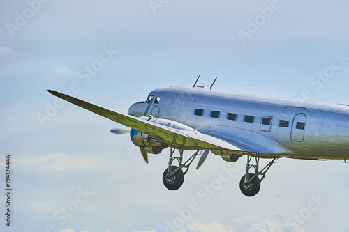 Old propeller airliner flying in cloudy sky Tablou Canvas