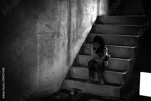 Fotografia Depressed young girl sitting alone in an abandoned building