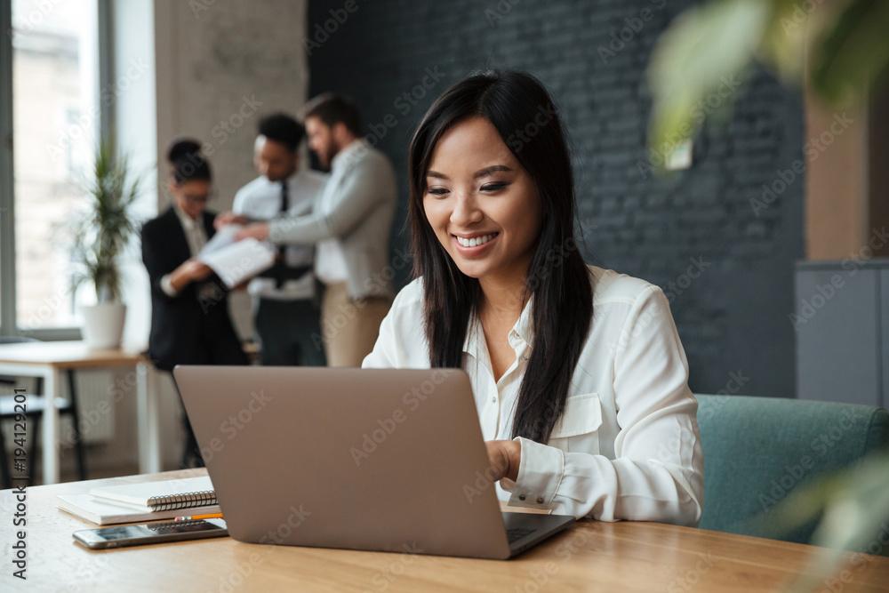 Fototapeta Cheerful young asian business woman using laptop