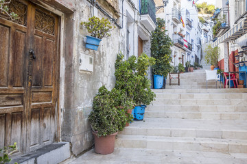 Fototapeta na wymiar  Colored picturesque houses, street.Typical neighborhood historic center, casco antiguo,barrio santa cruz.Alicante, Spain.