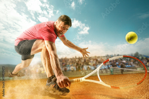 The one jumping player, caucasian fit man, playing tennis on the earthen court w Fotobehang