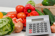 vegetables with a calculator on white table