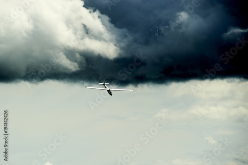 A Glider flying away from storm. The glider is a plane that has no engine.