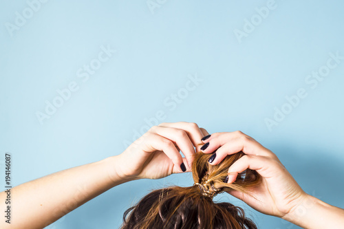 Fotografie, Obraz  The woman straightens the disheveled bun on her head with her hands with a black manicure