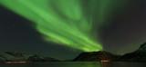 Fototapeta Na ścianę - Bright green Northern Light (Aurora Borealis) lighting up the dark skies above the mountains, Tromsø, Norway