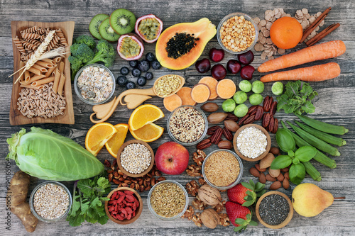 In de dag Assortiment High dietary fibre health food concept with fruit, vegetables, whole wheat pasta, legumes, cereals, nuts and seeds with foods high in omega 3, antioxidants, anthocyanins, smart carbs and vitamins.