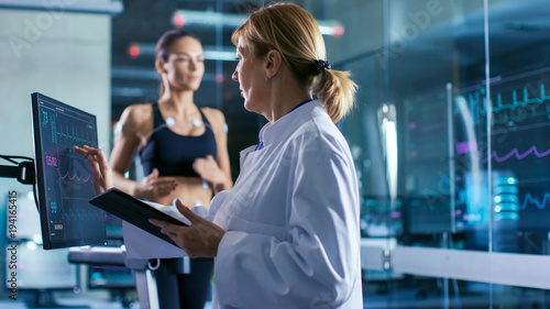 Fotografia  Sport Scientist Supervises Touches Display Showing EKG Status While in the Background Woman Athlete Running on a Treadmill with Electrodes Attached to His Body