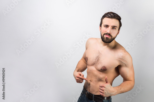 Foto  Good-looking and awesome guy is standing of a wall and pointing on himself and how his body is good