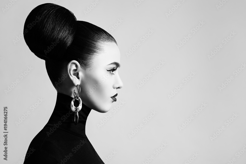 Fototapeta Retro style black and white fashion portrait of elegant female model with hair bun hairstyle and eyeliner makeup