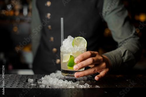 Fotografie, Obraz  Barman hand holding a glass filled with Caipirinha cocktail