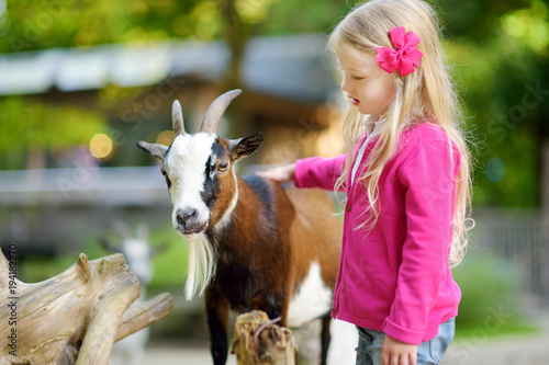 Fotografie, Obraz  Cute little girl petting and feeding a goat at petting zoo
