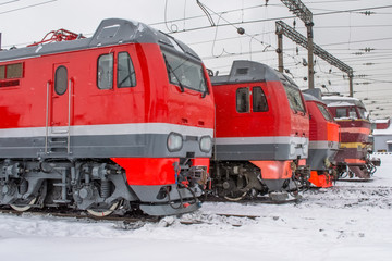 Electric locomotives are lined up on the railway in winter snow depot.