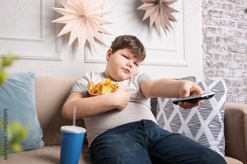 Cuadros en Lienzo  Overweight boy watching TV with snacks indoors