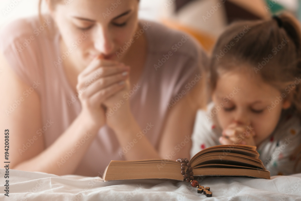 Fototapety, obrazy: Religious Christian girl and her mother praying over Bible indoors