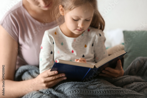 Obraz na płótnie Religious Christian girl reading Bible with mother indoors