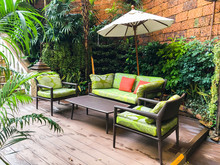 Cozy Sofa, Coffee Table And Umbrella In The Garden. Bali Style Decoration.