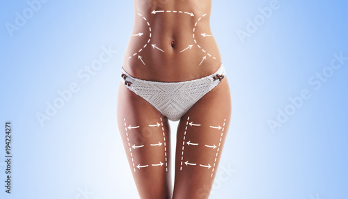 Fotografie, Obraz  Women slim body in swimwear having arrows along her stomach and legs