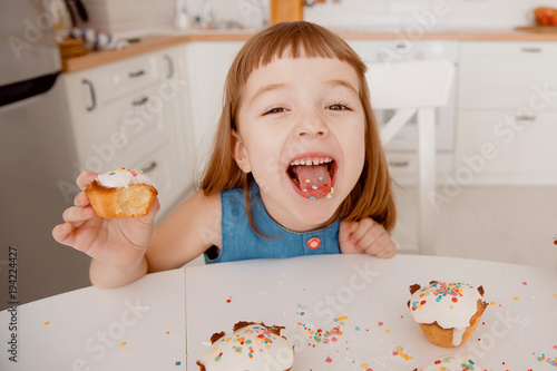 Close-up of color concentrates in tongue, in hand is a delicious cupcake, cooked by mom, fun and joy Poster