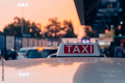 Fotografía Taxi sign on the roof of taxi cab on the busy street over yellow orange warming sunset background