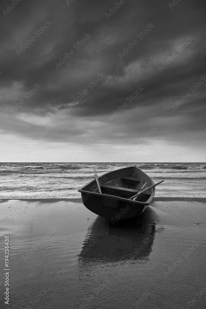 Fototapeta Small rowboat on beach, black and white