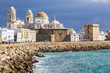 Views of Cádiz Cathedral (Catedral de Santa Cruz) from afar, with the coastline and the quay. Andalusia, Spain